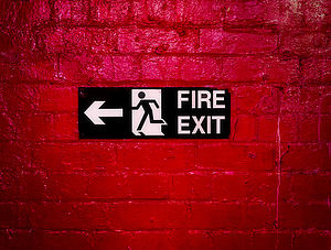 Sign Informing about the fire escape hung on a brick wall painted red.